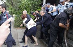 Julia-gillard-is-escorted-out-for-safety-by-body-guards-pic-ap-589516524